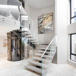 Immagine di una grande scala sospesa minimal con pedata acrillica, alzata in cemento e parapetto in metallo