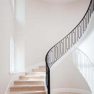 Cette image montre un grand escalier courbe traditionnel avec des marches en pierre calcaire, des contremarches en pierre calcaire et un garde-corps en métal.