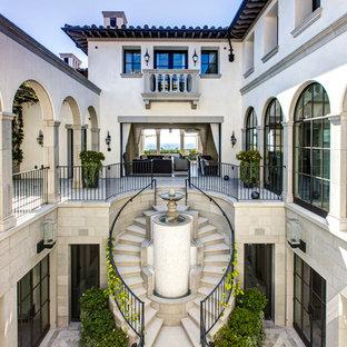 Стильный дизайн: изогнутая лестница в средиземноморском стиле с ступенями из известняка, подступенками из известняка и металлическими перилами - последний тренд