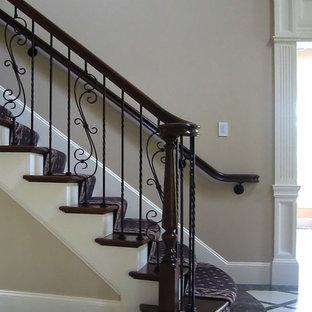 Foto de escalera curva, clásica, grande, con escalones de madera, barandilla de madera y contrahuellas de madera pintada