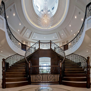 Staircase - huge traditional wooden curved staircase idea in Vancouver with wooden risers