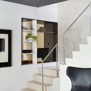 Ejemplo de escalera en L, actual, con escalones de madera, contrahuellas de madera y barandilla de vidrio