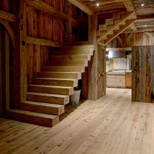 Large rural wood l-shaped staircase in New York with wood risers.