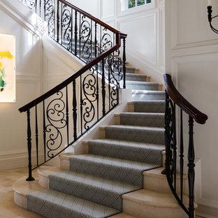 Ejemplo de escalera en U, tradicional, grande, con escalones enmoquetados, barandilla de madera y contrahuellas de mármol