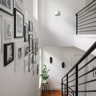 Cette image montre un escalier sans contremarche droit nordique de taille moyenne avec des marches en bois et un garde-corps en métal.