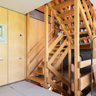 This is an example of a medium sized midcentury wood u-shaped wood railing staircase in London with open risers.
