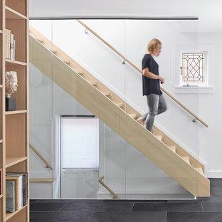 Inspiration pour un escalier droit nordique avec des marches en bois et un garde-corps en verre.