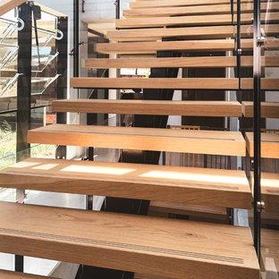 シドニーの広い木のコンテンポラリースタイルのおしゃれな直階段 (ガラスの蹴込み板、混合材の手すり) の写真