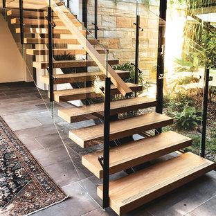 Esempio di una grande scala a rampa dritta design con pedata in legno, alzata in vetro e parapetto in materiali misti
