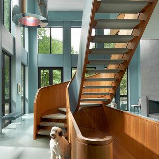 На фото: изогнутая лестница в стиле современная классика с деревянными перилами без подступенок с