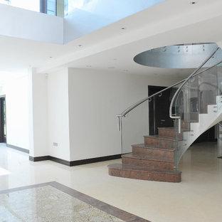 ロンドンの大理石のコンテンポラリースタイルのおしゃれな階段 (ガラスの手すり、大理石の蹴込み板) の写真