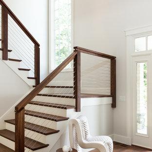 На фото: большая п-образная лестница в стиле неоклассика (современная классика) с деревянными ступенями, крашенными деревянными подступенками и перилами из тросов