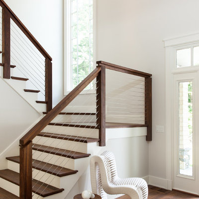 Large transitional wooden u-shaped cable railing staircase photo in Boston with painted risers