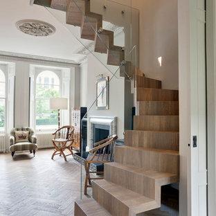Imagen de escalera suspendida, bohemia, de tamaño medio, con escalones de madera, contrahuellas de madera y barandilla de vidrio