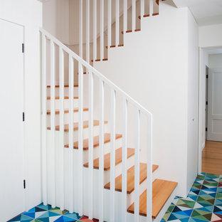Ejemplo de escalera en U, escandinava, con escalones de madera, contrahuellas de madera y barandilla de madera