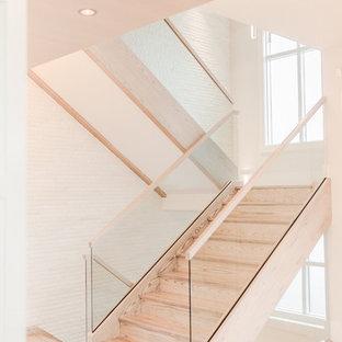 """Immagine di un'ampia scala a """"U"""" minimal con pedata in legno e alzata in legno"""