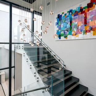 Idées déco pour un escalier moderne de taille moyenne avec des marches en bois et des contremarches en verre.
