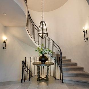 他の地域の広いライムストーンの地中海スタイルのおしゃれなサーキュラー階段 (ライムストーンの蹴込み板、金属の手すり) の写真
