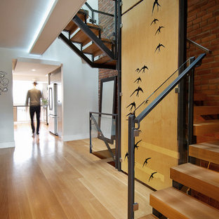 Imagen de escalera curva, urbana, de tamaño medio, sin contrahuella, con escalones de madera y barandilla de metal