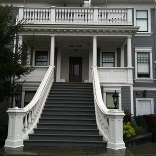 На фото: огромная изогнутая лестница с крашенными деревянными ступенями и крашенными деревянными подступенками