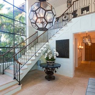 Imagen de escalera mediterránea con escalones con baldosas, contrahuellas de madera pintada y barandilla de metal