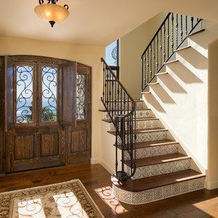 Ejemplo de escalera en U, mediterránea, de tamaño medio, con escalones de madera y contrahuellas con baldosas y/o azulejos