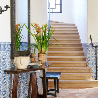 Staircase - mediterranean wooden curved metal railing staircase idea in Santa Barbara with wooden risers