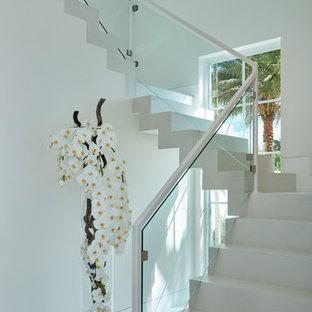 Modelo de escalera curva, actual, grande, con escalones de madera pintada y contrahuellas de madera pintada