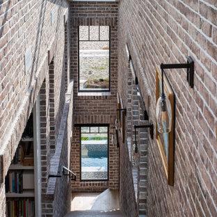Diseño de escalera recta y ladrillo, marinera, grande, con escalones de madera, contrahuellas de madera, barandilla de metal y ladrillo