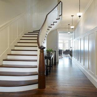 Esempio di una scala curva vittoriana di medie dimensioni con pedata in legno, alzata in legno verniciato e parapetto in legno