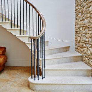 Modelo de escalera curva, minimalista, grande, con escalones de mármol y contrahuellas de metal