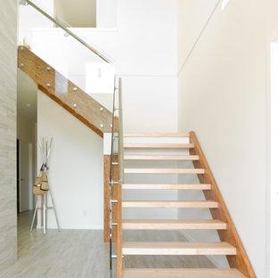 Ejemplo de escalera en L, minimalista, de tamaño medio, sin contrahuella, con escalones de madera y barandilla de vidrio