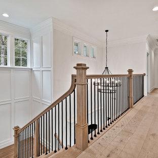 Foto de escalera en U y boiserie, de estilo americano, grande, con escalones de madera, contrahuellas de madera, barandilla de varios materiales y boiserie