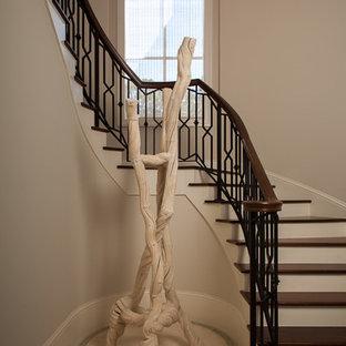 Новые идеи обустройства дома: огромная изогнутая лестница в стиле современная классика с деревянными ступенями и деревянными подступенками
