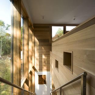 Foto på en liten funkis rak trappa i trä, med sättsteg i trä och kabelräcke