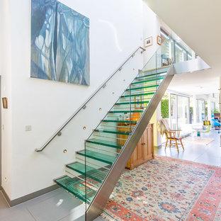 Foto de escalera recta, actual, sin contrahuella, con escalones de vidrio y barandilla de vidrio