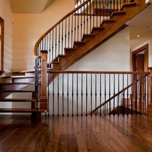 Ejemplo de escalera curva, de estilo americano, de tamaño medio, sin contrahuella, con escalones de madera