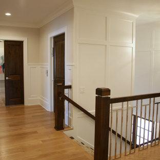 Diseño de escalera en L y panelado, clásica renovada, grande, con escalones de madera, contrahuellas de madera pintada, barandilla de metal y panelado