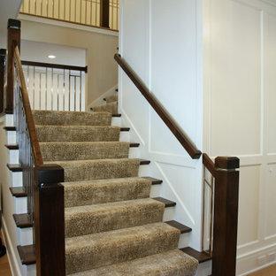 Imagen de escalera en L y panelado, tradicional renovada, grande, con escalones de madera, contrahuellas de madera pintada, barandilla de metal y panelado