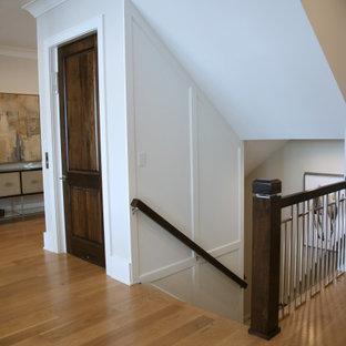 Foto de escalera en L y panelado, clásica renovada, grande, con escalones de madera, contrahuellas de madera pintada, barandilla de metal y panelado