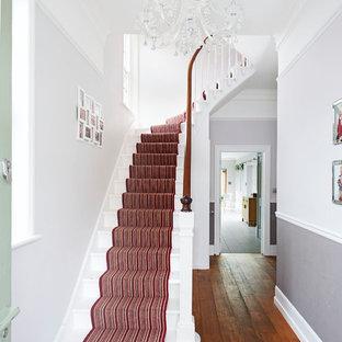 Пример оригинального дизайна: изогнутая лестница в стиле современная классика с крашенными деревянными ступенями, крашенными деревянными подступенками и деревянными перилами