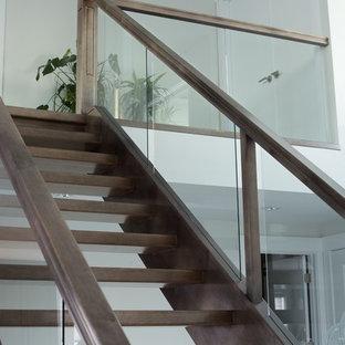 カルガリーの木のモダンスタイルのおしゃれな直階段 (木の蹴込み板、木材の手すり) の写真