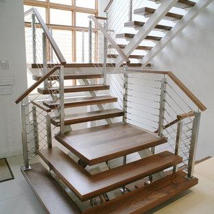 Foto di una scala sospesa minimalista di medie dimensioni con pedata in legno e nessuna alzata