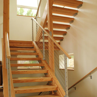 Diseño de escalera suspendida, actual, de tamaño medio, con escalones de madera, contrahuellas de madera y barandilla de cable
