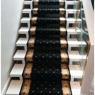 Imagen de escalera suspendida, clásica, grande, con escalones de madera pintada y barandilla de vidrio