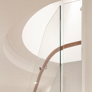 Ejemplo de escalera curva y papel pintado, marinera, grande, con escalones de madera, contrahuellas de madera pintada, barandilla de madera y papel pintado