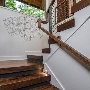 """Immagine di una scala a """"U"""" minimalista di medie dimensioni con pedata in legno, parapetto in cavi e alzata in legno"""