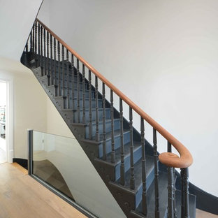 Huge trendy painted curved staircase photo in Kent with painted risers