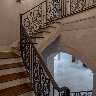 Imagen de escalera en L, rústica, extra grande, con escalones de madera, contrahuellas de madera pintada y barandilla de metal