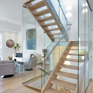 トロントの中くらいの木のコンテンポラリースタイルのおしゃれな階段 (ガラスの手すり) の写真